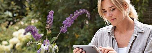 Woman sitting with a tray at a garden table with lilac twigs and dishes